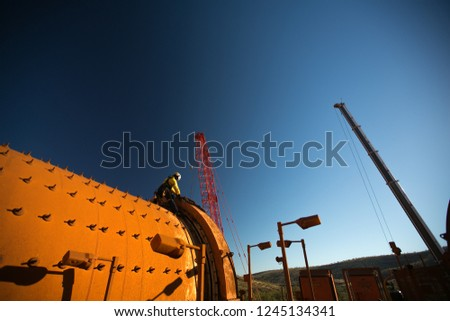 Rope access inspector technician abseiler working at height setting working in fall arrest position, performing chute inspection maintenance, construction mine site, Perth, Australia