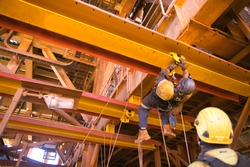 Rope access maintenance worker wearing safety harness hard hat working at height descending on rope performing inspecting monorail trolley connect with beam clamp prior to use construction site Perth