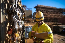 Rope access miner technician inspector inspecting safety checklist on ropes descenders,locking carabiners hardware equipment making sure prior to commencing work at construction site Perth, Australia