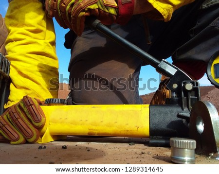 Rope access technician engineer worker hand holding pushing pull tester handle while testing pulling lifting lug load prior to lifting heavy loads construction mine site, Perth, Australia  #1289314645