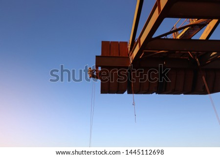 Rope access technician inspector abseiling working at height and placing safety rope protection on sharp edges during concrete spalling inspection on counterweight construction site Sydney, Australia