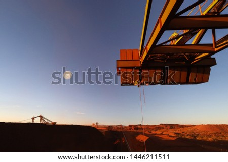 Rope access technician inspector wearing fall body safety harness abseiling working at height inspecting defect of concrete spalling counterweight during sunset with fall moon rising at the background