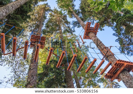 Rope adventure park in a summer forest scenic blue sky scenery. Overcoming obstacles and reaching heights abstract concept ストックフォト ©