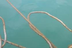 Rope floating on surface of the deep blue sea background. covered with algae.