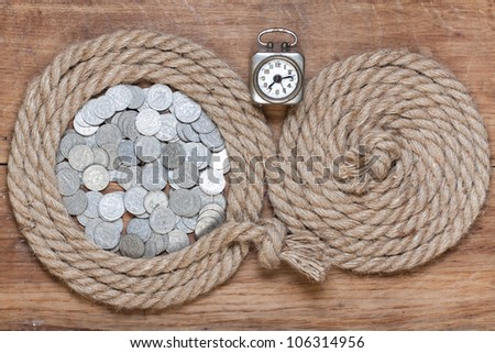 Rope frame, vintage clock, antique coins, on oak wood texture