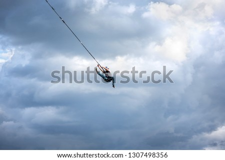 Rope jumping from high altitude bridge. Concept of overcoming fear, courage, active lifestyle, excitement, adventures and adrenaline. Summer sports festival outdoors. Young man having fun