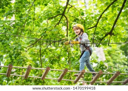Photo of  Rope park - climbing center. Child boy having fun at adventure park. Go Ape Adventure. Child boy having fun at adventure park.
