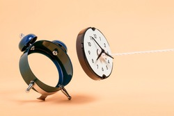 rope pulling out clock face from alarm clock, abstract time concept