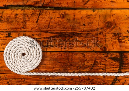 Rope, Textured Wood, Copy Space - Coiled, white rope on a highly textured wooden background.  Copy space on right.  Nautical theme.