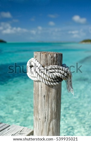 Rope tied to a post on a dock in the ocean.