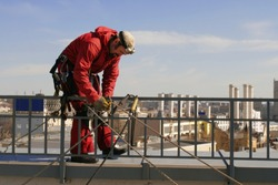 Rope worker on the roof of one building in the Moscow