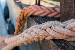 Ropes on Old Rusty Ship Closeup. Old Frayed Boat Rope as a Nautical Background. Naval Ropes on a Pier. Vintage Nautical Knots. Big Marine Sea Ship Ropes.