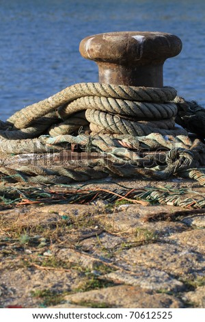 Ropes rolled up around rusty metal bitt