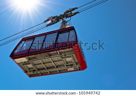 Ropeway wagon moving to the mountain peak with blue sky on background