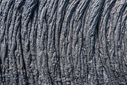 Ropey lava is a result of the front flow slowing down and the back flow speeding up, causing the lava to roll over itself and forming rope shapes.