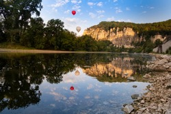 Roque-Gageac, Dordogne, France. Hot air balloons in the early morning float over the tufa cliffs and the dordogne river