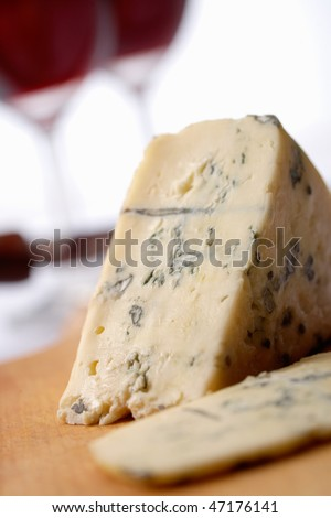 Roquefort soft blue french cheese.  A wine at background