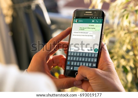 ROSARIO, ARGENTINA -AUGUST 8, 2017: Girl with smartphone in her hands and a whatsapp conversation on the screen. Young woman, millennial, chatting. Technology. Communications.