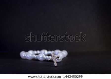 Rosary beads and cross on black surface #1443450299