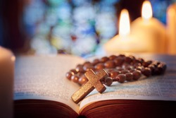 Rosary beads and crucifix cross on holy bible with candles in church