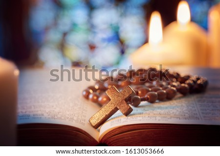 Rosary beads and crucifix cross on holy bible with candles in church Stock photo ©