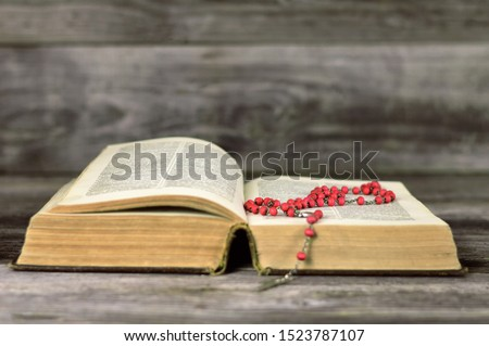 Rosary beads and holly bible on wooden background #1523787107