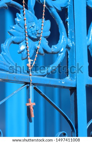 Rosary beads hanging on a blue church gate #1497411008