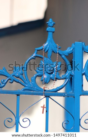 Rosary beads hanging on a blue church gate #1497411011