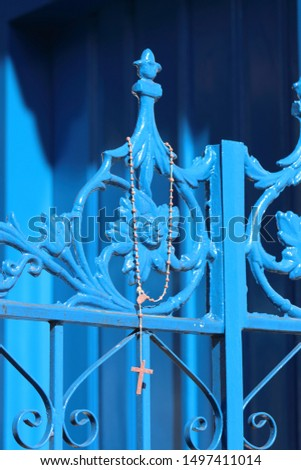 Rosary beads hanging on a blue church gate #1497411014