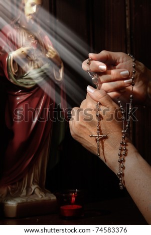 Rosary beads, light rays falling on hands