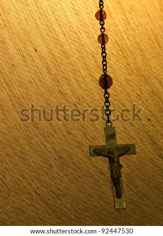 Rosary Chain hanging from a lamp shade. - stock photo