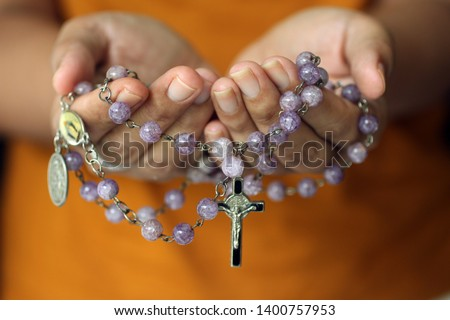 Rosary in hand. Young junior lady holding rosary with open hand. Female hands holding a rosary with Jesus Christ Cross Crucifix. Month of Rosary, Christian Catholic religious symbol of faith concept. Stock photo ©