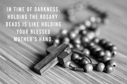 Rosary inspirational quote - In time of darkness, holding the rosary beads is like holding your blessed mothers hand. With Rosary and Jesus Christ holy cross crucifix in black and white background.