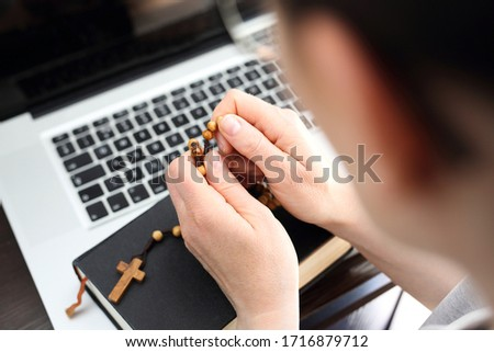 Rosary prayer online, holy mass conducted online. A woman prays on a rosary in front of a computer.
