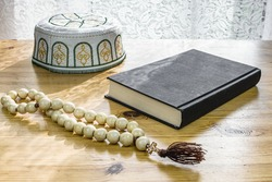Rosary with a wooden cross . book on the table