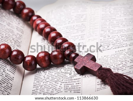 rosary with a wooden cross lying on open Bible