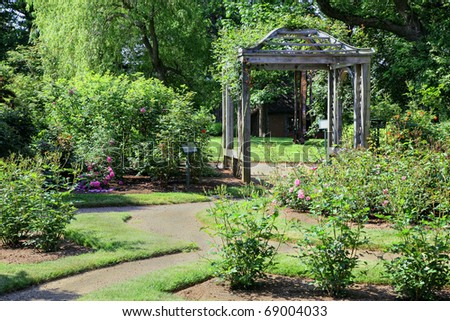 Rose arbor in a formal rose garden in spring.
