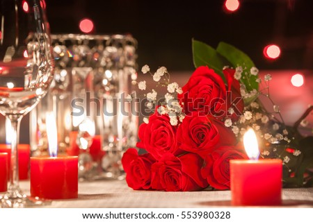 Rose bouquet in a romantic candle light setting table. Love and romance concept.  #553980328