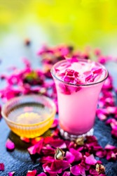 Rose falooda or rose shake in a transparent glass along with some honey in another bowl on wooden surface,Popular summer and ramazan or Ramadan drink.