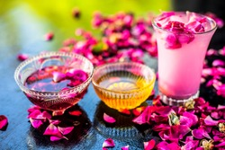 Rose falooda or rose shake in a transparent glass on wooden surface along with some honey and rose syrups in different bowls.Some rose petals on the glass also for as garnish.