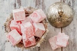 Rose flavoured Turkish delight in traditional silver bowl on wooden white background