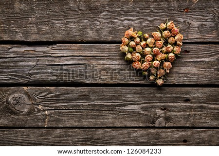 Rose flowers in heart shape on old wooden plates. Sweet holiday background