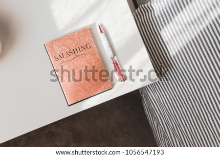Rose gold glitter notebook and pen on a white table. Woman's stylish accessories. Blogging, freelance, minimalism lifestyle concept