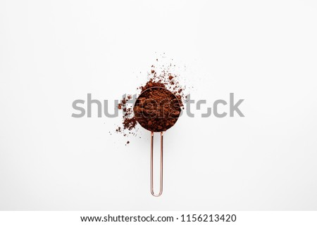 Rose gold measuring cup of cocoa powder on a white background, healthy food concept