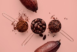 Rose gold measuring cups of cocoa beans, cacao nips, cocoa powder and cocoa pods on a pink background, flat lay healthy food concept