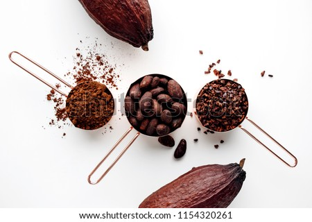 Rose gold measuring cups of cocoa beans, cacao nips, cocoa powder and cocoa pods on a white background, flat lay healthy food concept