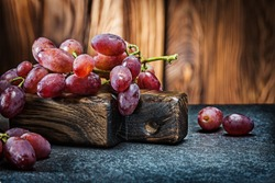 rose grape little branch on vintage carving board and wooden background