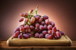 rose grape on wooden cutting board and brown gradient background
