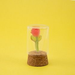Rose Gummy candy product shot. Inspired by Beauty and the Beast rose scene. Shot in a glass container on a yellow background.