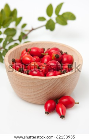 Rose hip branch with leaves in wooden bowl